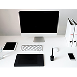 Closeup image of a computer with blank screen and gadgets on the table in office